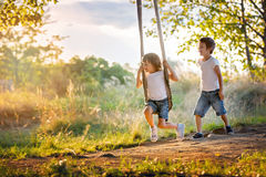 Two children, boy brothers, having fun on a swing in the backyar Royalty Free Stock Photo