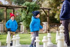 Two children, boy brothers, playing chess with huge figures in t. He park on the ground, autumn time. Childhood happiness concept, kids playing in the park fall Royalty Free Stock Photography