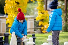Two children, boy brothers, playing chess with huge figures in t. He park on the ground, autumn time. Childhood happiness concept, kids playing in the park fall Stock Photography