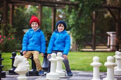 Two children, boy brothers, playing chess with huge figures in t. He park on the ground, autumn time. Childhood happiness concept, kids playing in the park fall Royalty Free Stock Images