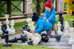 Two children, boy brothers, playing chess with huge figures in t. He park on the ground, autumn time. Childhood happiness concept, kids playing in the park fall Royalty Free Stock Photo