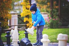 Two children, boy brothers, playing chess with huge figures in t. He park on the ground, autumn time. Childhood happiness concept, kids playing in the park fall Stock Images