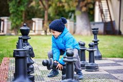 Two children, boy brothers, playing chess with huge figures in t. He park on the ground, autumn time. Childhood happiness concept, kids playing in the park fall Stock Photos