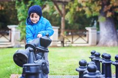 Two children, boy brothers, playing chess with huge figures in t. He park on the ground, autumn time. Childhood happiness concept, kids playing in the park fall Royalty Free Stock Image