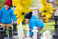 Two children, boy brothers, playing chess with huge figures in t. He park on the ground, autumn time. Childhood happiness concept, kids playing in the park fall Royalty Free Stock Photos