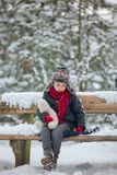 Two children, boy brothers, sitting on a bench in park, winterti Royalty Free Stock Images