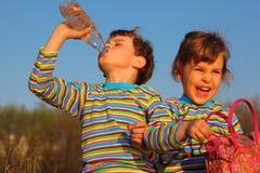 Two children: boy drinks, girl holds bag Stock Image