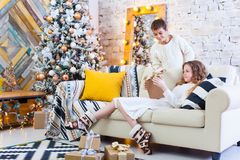 Two children a boy and a girl at a Christmas tree on a sofa with gifts. In light colors. give presents to each other. Two children a boy and a girl at a Royalty Free Stock Images