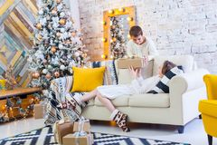 Two children a boy and a girl at a Christmas tree on a sofa with gifts. In light colors. give presents to each other. Two children a boy and a girl at a Stock Image
