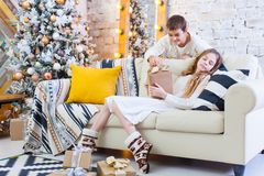Two children a boy and a girl at a Christmas tree on a sofa with gifts. In light colors. give presents to each other. Two children a boy and a girl at a Royalty Free Stock Photography