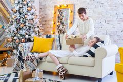 Two children a boy and a girl at a Christmas tree on a sofa with gifts. In light colors. give presents to each other. Two children a boy and a girl at a Stock Photos