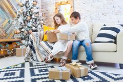Two children a boy and a girl at a Christmas tree on a sofa with gifts. In light colors. spying on each other`s gift. Two children a boy and a girl at a Royalty Free Stock Images