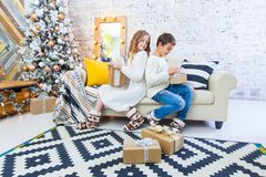 Two children a boy and a girl at a Christmas tree on a sofa with gifts. In light colors. spying on each other`s gift. Two children a boy and a girl at a Royalty Free Stock Image