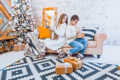 Two children a boy and a girl at a Christmas tree on a sofa with. Gifts. In light colors spying on each other`s gift Stock Image