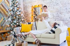 Two children a boy and a girl at a Christmas tree on a sofa with gifts. In light colors. give presents to each other. Two children a boy and a girl at a Royalty Free Stock Image