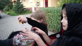 Two children, boy and girl, in dark costumes for Halloween take candies. Halloween. Trick or Treat. Boy in a black-red cloak of the magician and girl in suit of stock footage