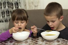 Two children boy and girl eating soup with spoon from a plate wi Stock Image