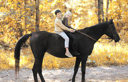 Two children boy and girl riding on horse in autumn Stock Image