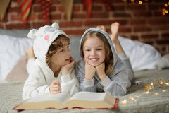 Two children, brother and sister, read Christmas tales. Royalty Free Stock Images