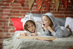 Two children, brother and sister, read Christmas tales. Stock Photography