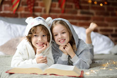 Two children, brother and sister, read Christmas tales. Stock Photo