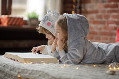 Two children, brother and sister, read Christmas tales. Royalty Free Stock Photography