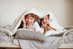 Two children, brother and sister, squirmy on the bed in the bedroom. Stock Photography