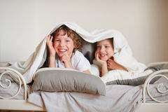 Two children, brother and sister, squirmy on the bed in the bedroom. Stock Images