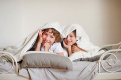 Two children, brother and sister, squirmy on the bed in the bedroom. Royalty Free Stock Images
