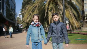 Two children, brother and sister. twins walking in the park on the alley stock footage