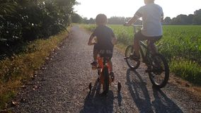 Children with bike in park. Two children brothers play with the bikes in a park in a dusty road stock video