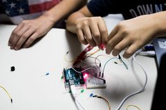 Two children build a prototype circuit with a red laser controlled by a microcontroller. STEAM and coding activity royalty free stock photos