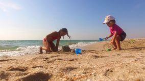 Two Children Building Sand Castle On The Beach. This is a low angle shot of two children - little girl and little boy playing with sand on the beach building a stock footage