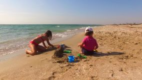 Two Children Building Sand Castle On The Beach stock video footage