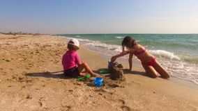 Two Children Building Sand Castle On The Beach stock video