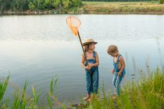 Two children with a butterfly net near the river stock photography