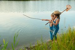 Two children with a butterfly net near the river royalty free stock image