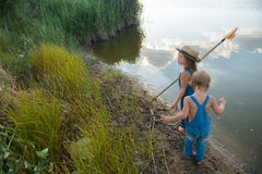 Two children with a butterfly net near the river stock image