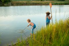 Two children with a butterfly net near the river royalty free stock photo