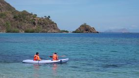 Two children canoeing on beach. Happy two children enjoying holiday together by canoeing on the beach with beautiful landscape in Labuan Bajo at Flores Island stock video footage