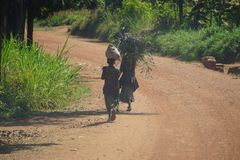Two children carry branches and bag as walk down dusty road royalty free stock photo