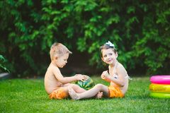 Two children, Caucasian brother and sister, sitting on green grass in backyard of house and hugging big tasty sweet watermelon stock photography