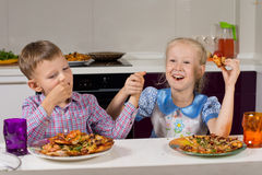 Two children celebrating eating their pizza Royalty Free Stock Photography