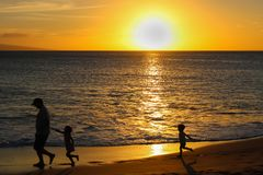 Children in Silhouette Chase Father on Beach at Sunset stock photo