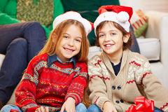 Two children with christmas hats Stock Photos