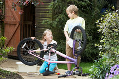 Two Children Cleaning Bike Together Stock Photography