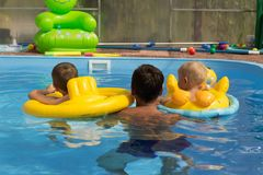 Two children with a coach, with dad learn to swim in the pool, rear view. cares, vacation. inflatable circles. Lifebuoy stock photo