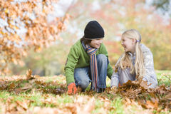 Two children collecting leaves Stock Photos