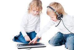 Two children with computer on floor isolated Royalty Free Stock Images