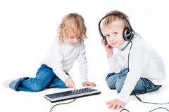 Two children with computer on floor isolated Stock Photography